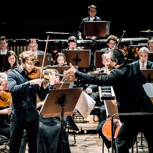 dyrygent wskazujący na skrzypka-solistę, w tle orkiestra