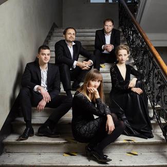dwie kobiety i trzech mężczyzn siedzących na schodach