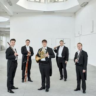 pięciu muzyków z instrumentami ubranych we fraki