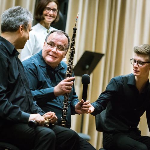 trzech muzyków po koncercie, jeden z nich trzyma obój i mikrofon w ręku, w tle prowadząca koncert
