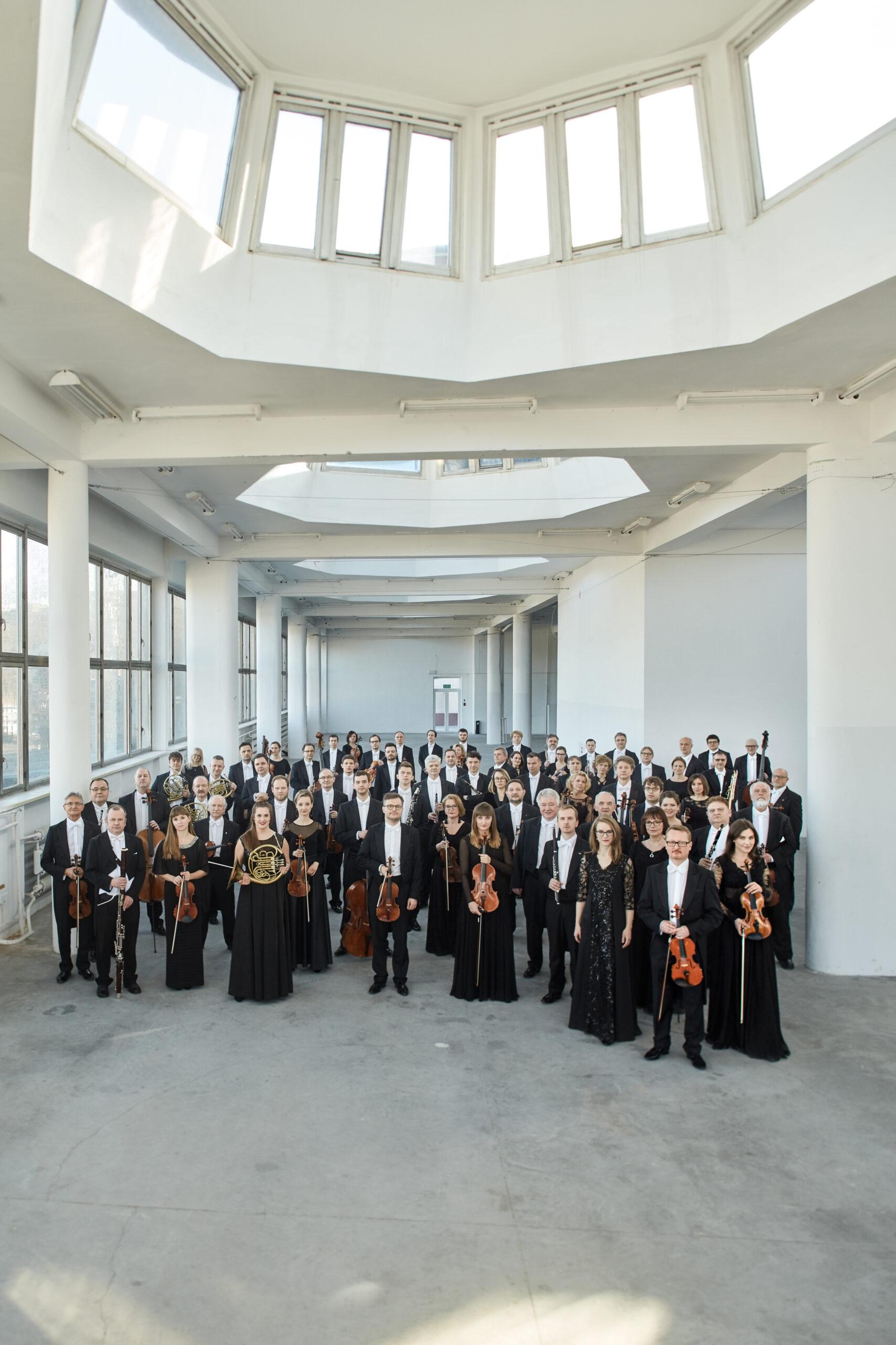 orkiestra sinfonia varsovia ludzie z instrumentami w czarnych strojach na tle białych ścian