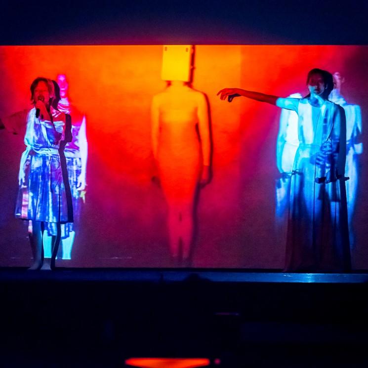 Kadr z utworu audiowizualnego, dwie performerki stoją na tle projekcji