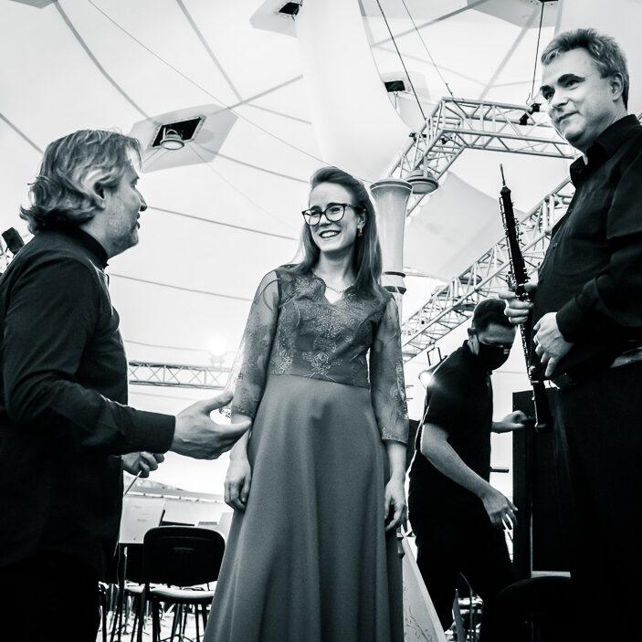 od lewej dyrygent, harfistka i oboista, dyrygent w trakcie rozmowy z muzykami