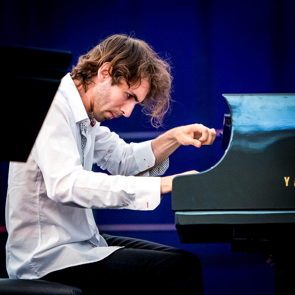 pianista w trakcie gry, z uniesioną lewą dłonią