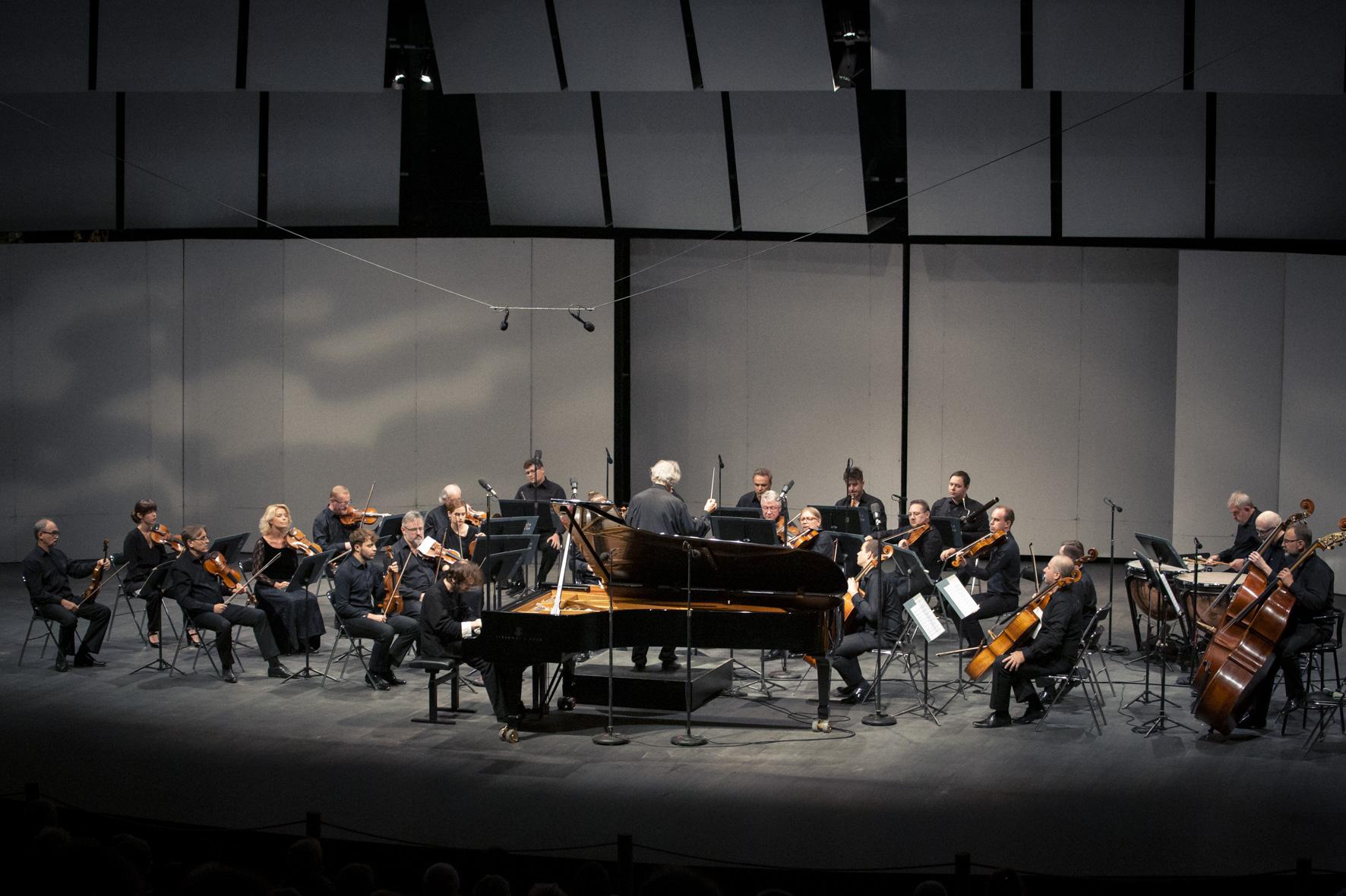 Muzycy orkiestry wraz zsolista idyrygentem grają nascenie wczasie koncertu