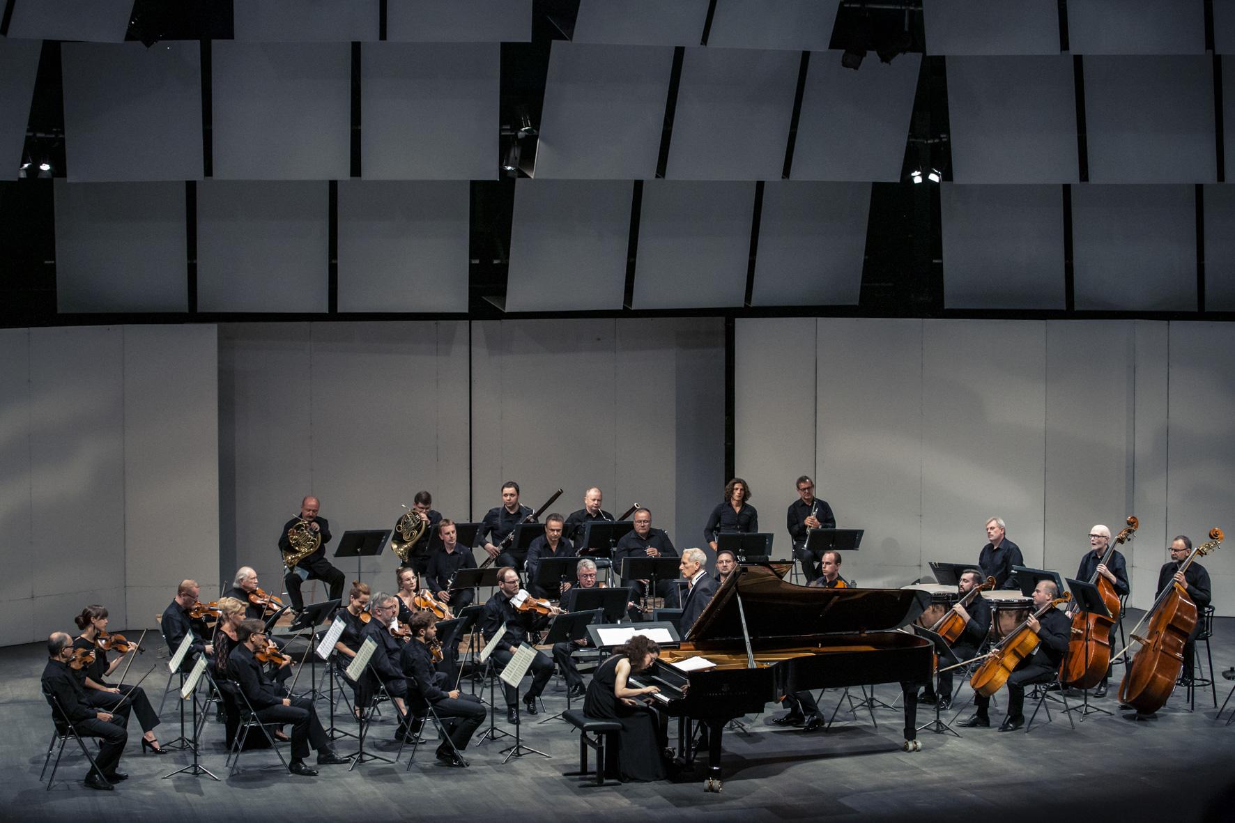 Muzycy orkiestry zdyrygentem isolistą grają wczasie koncertu